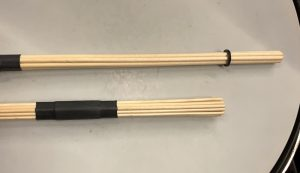 Two multi-rod drumsticks. One is longer and has fewer sticks than the other.