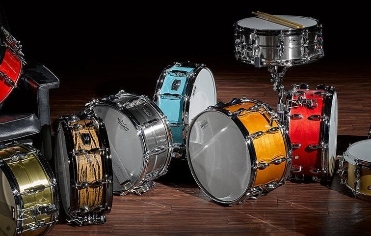 A collection of snare drums arranged haphazardly on a darkened stage.