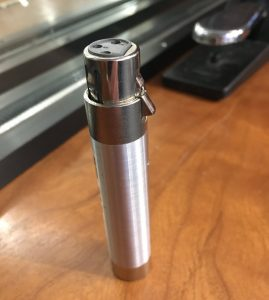 Closeup of inline pad - a small cylinder with closed end with three perforations.