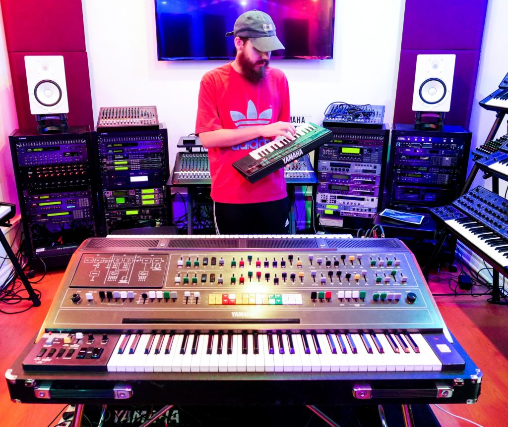 Artist San Holo holds his VSS-30 sampler in a room with a collection of vintage Yamaha synthesizers.