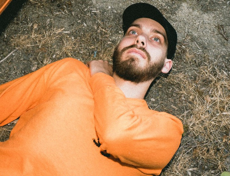 Bearded young man in long sleeved t-shirt and billed cap laying on ground staring upwards.