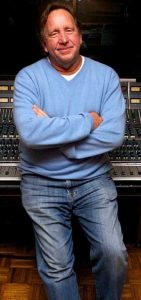 Middle-aged man in jeans and sweater casually leaning against a sound board.