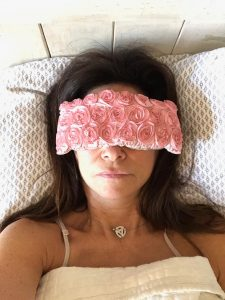 Shelly Peiken laying face up in bed wearing a floral eye mask.