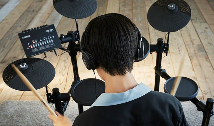 Youth practicing on an electronic drum kit.