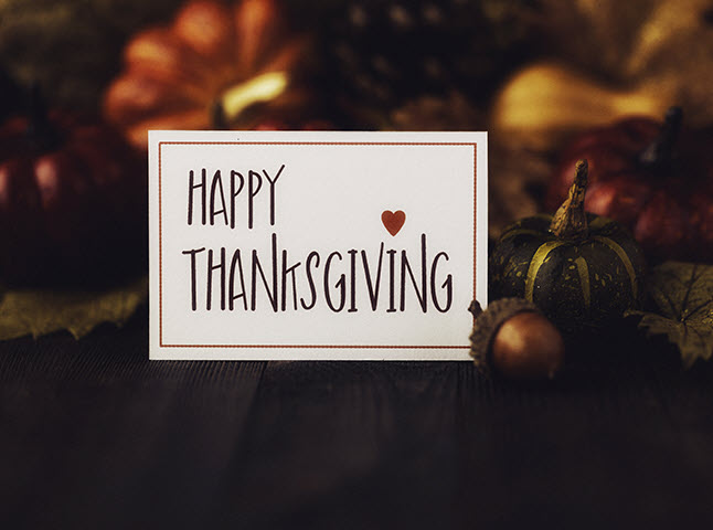"""Card with words """"Happy Thanksgiving"""" imposed on a collection of crafted items representing fall: acorn, squash, etc."""