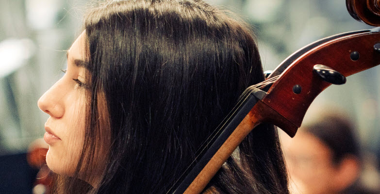 Closeup of young women holding a large string instrument.