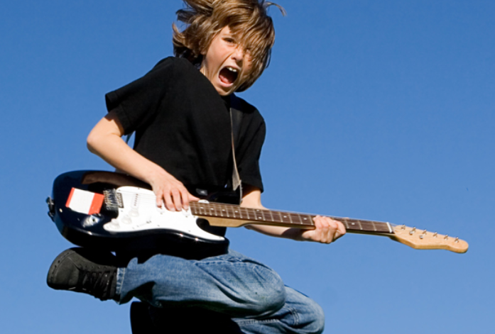 Young boy jumping in air while playing electric guitar.