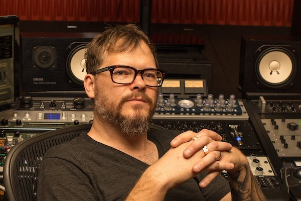 Mastering engineer in studio sitting in front of mixing console.