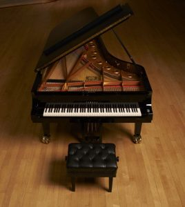 Yamaha CFX grand piano on wooden stage.