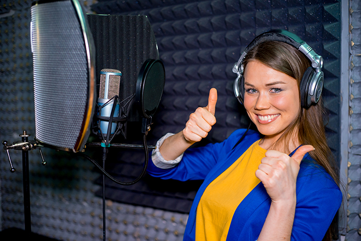A portrait of a singer in a recording studio giving the thumbs up a curved screen positioned behind the vocal mic.