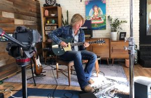 Robbie Calvo playing an electric guitar in front of a camera.