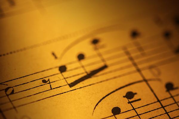 Detail of music sheet under golden light.