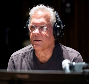 Music producer wearing headphones, looking thoughtfully into the distance.
