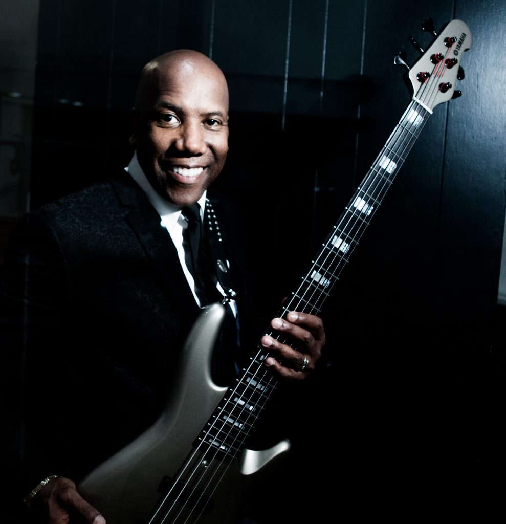 Nathan East smiling while holding his signature Yamaha bass.