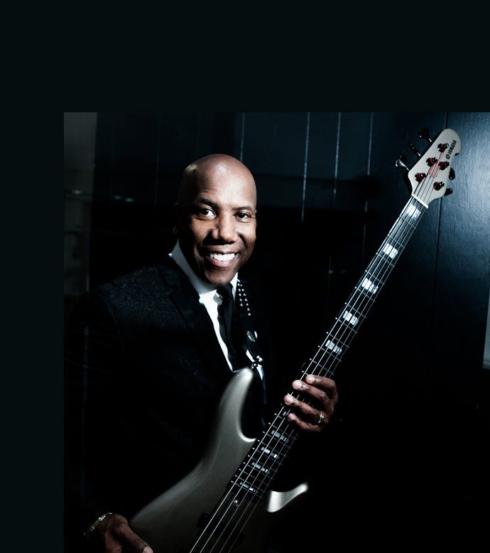 Professional shot of smiling man in suit holding electric guitar.