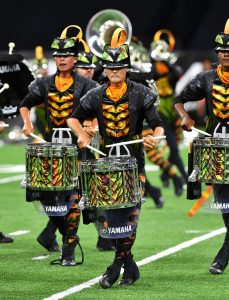 Drummers in elaborate costumes with matching drums march through stadium.