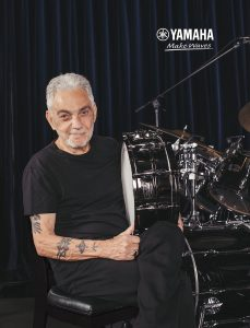 Tattooed man with white hair holding snare drum, sitting next to drum kit in front of purple curtains.