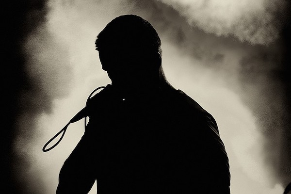 Silhouette of the singer holding microphone and singing on the stage during rock and roll concert.