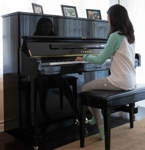 Young girl plays upright piano in living room.