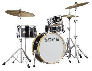 Black drum set with bass drum, two tom drums, snare drum, two cymbals & a hi-hat.