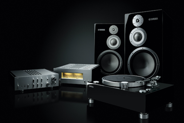 Various Yamaha products including an amplifier, preamplifier, two speakers and turn table set on black background.