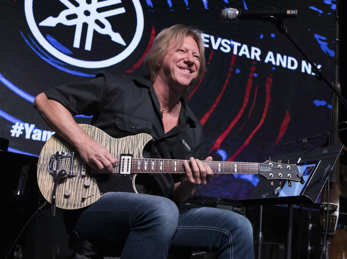 Robbie Calvo smiling at camera while holding an electric guitar.