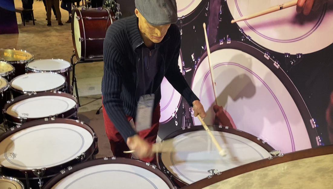 Man with grey flat cap plays extra-large concert drums.