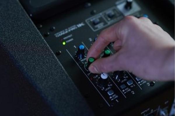 Hand adjusting dial on Yamaha STAGEPAS mixer.