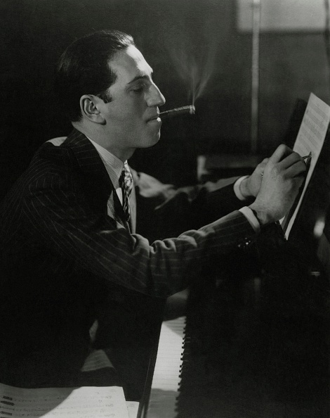 American composer George Gershwin sitting at a piano, smoking a cigar and writing on sheet music.