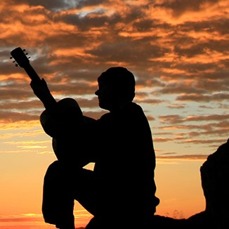 Silhouette of a man playing guitar in front of a beautiful sunset.