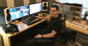 A man sitting in a sound design studio.