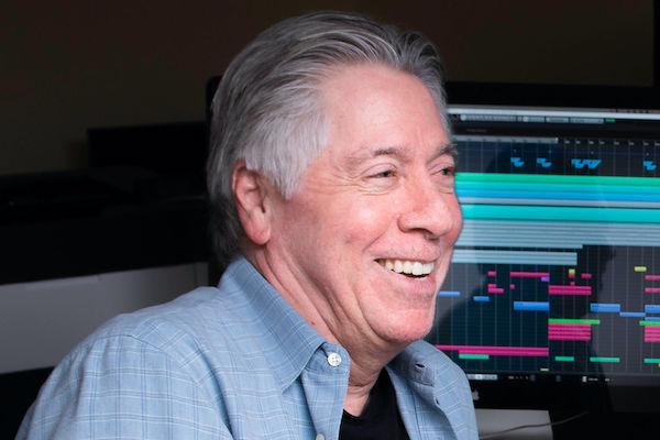 Alan Silvestri smiling in studio in front of monitors.