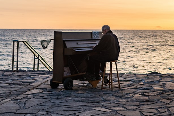 Elderly man playing a piano in front of the ocean.