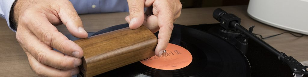 Man using using an anti-static cleaning brush to clean vinyl record.