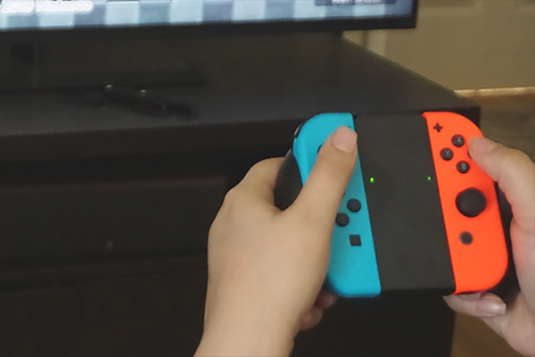Person holding switch controller near tv screen.