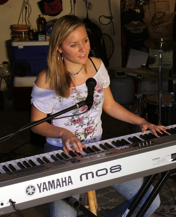 Young woman at home playing a Yamaha synthesizer.