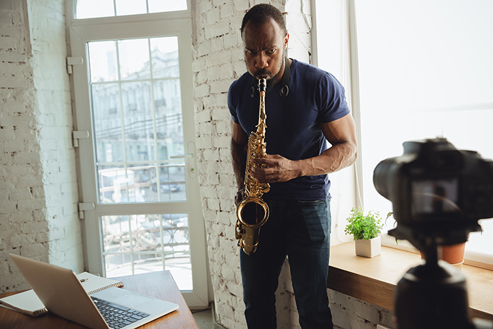 Musician playing saxophone during online concert at home isolated and quarantined.