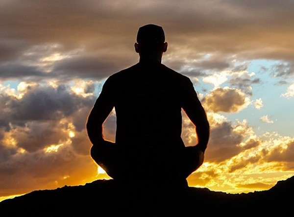 Silhouette of man sitting in lotus position watching the sunset.