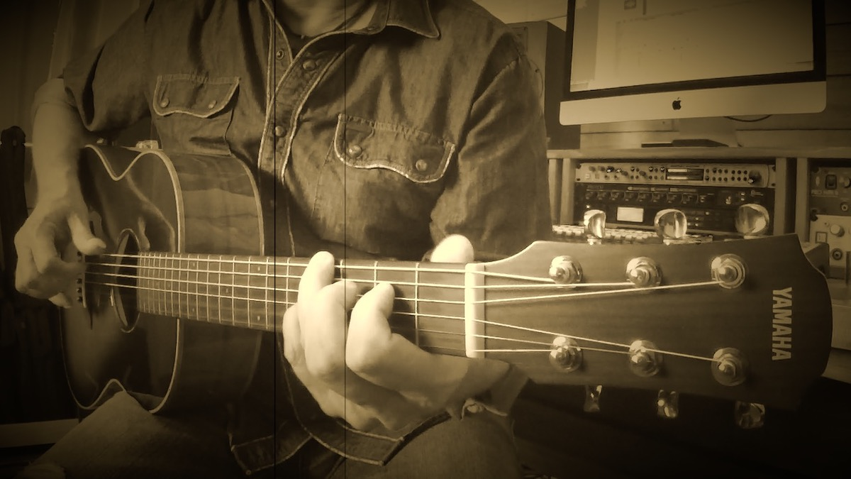 Man playing guitar with vintage-style photo filter.