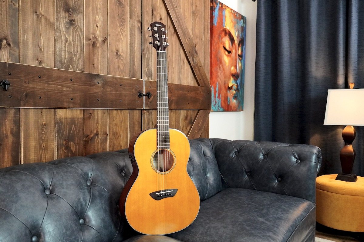 TransAcoustic guitar resting on dark leather couch.