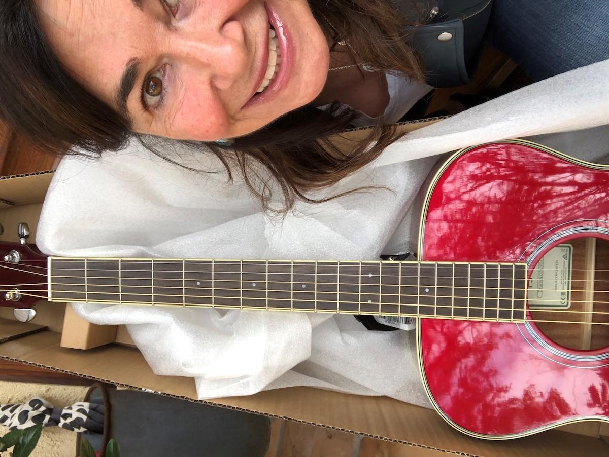 Shelly Peiken holding red FS-TA guitar.