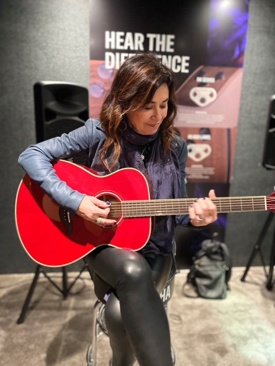 Shelly Peiken holding red FS-TA guitar at NAMM.
