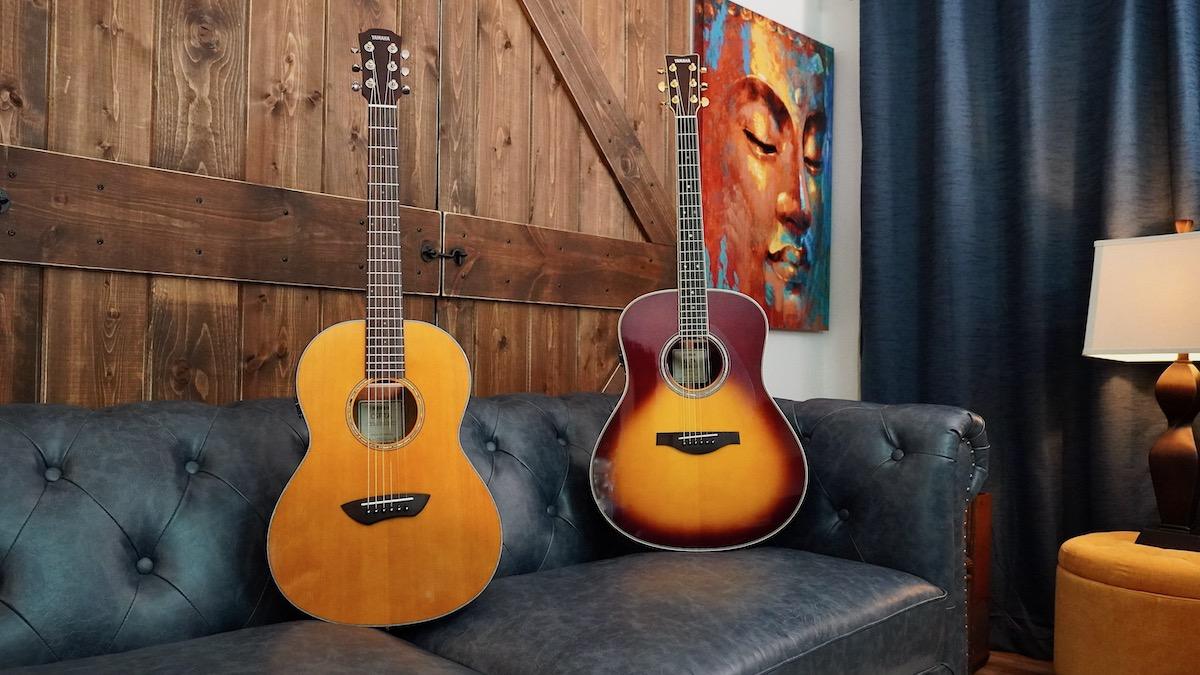 Two Yamaha TransAcoustic guitars resting on a leather couch.