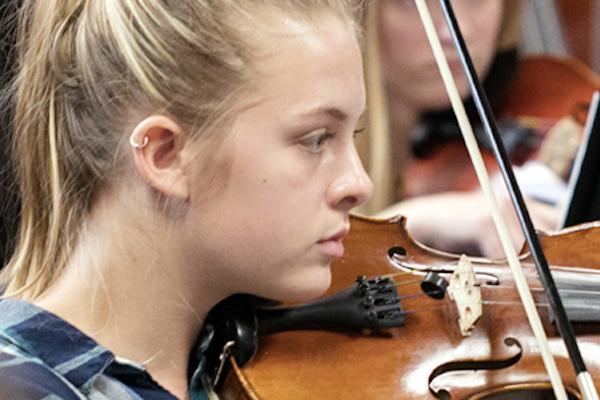 Young girls playing violin.