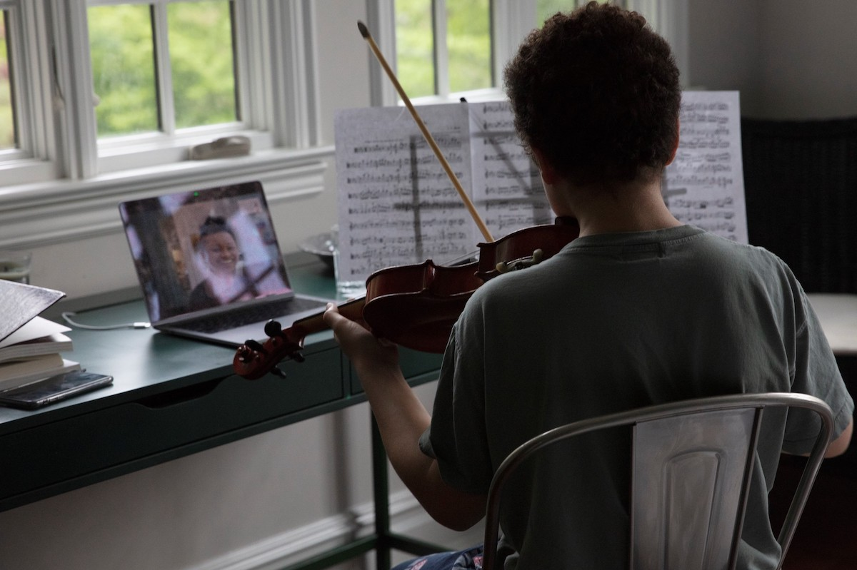 Young boy studying violin with virtual lesson.