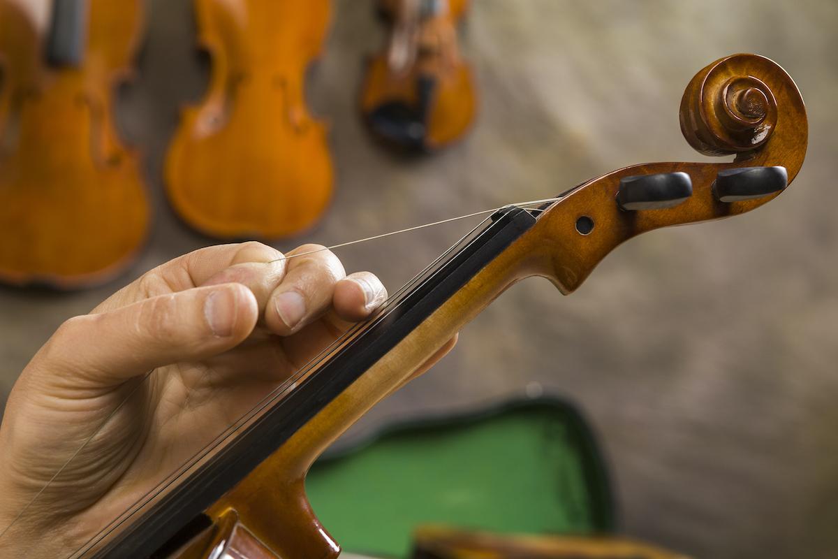 Instrument maker repairing old violin in studio.