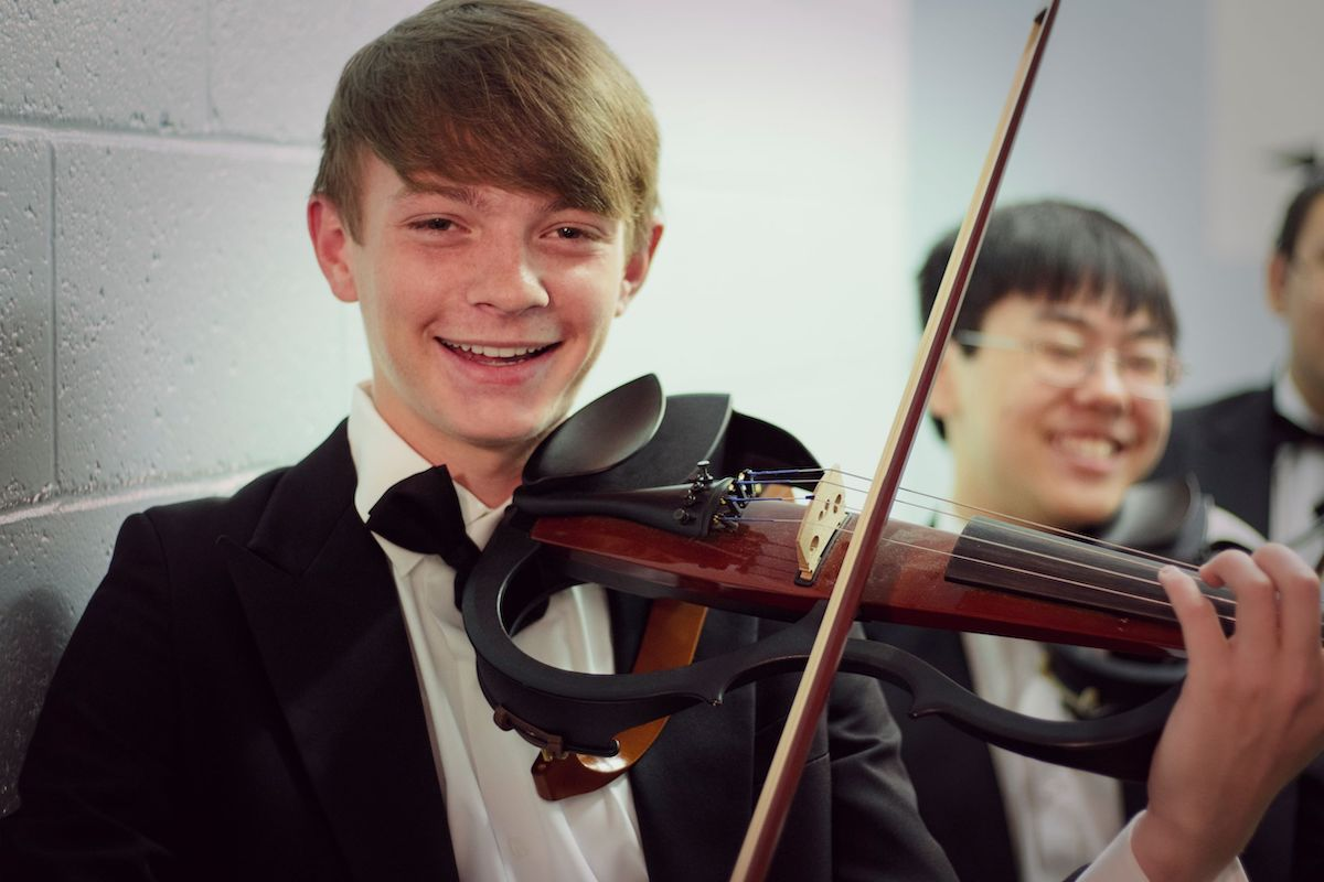 Young student plays electric violin with other young men.