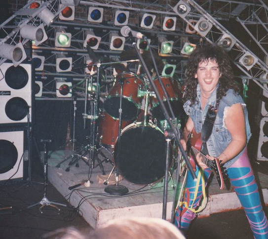 Butch Walker in his early shredding days with gaudy clothing and large curly hair.