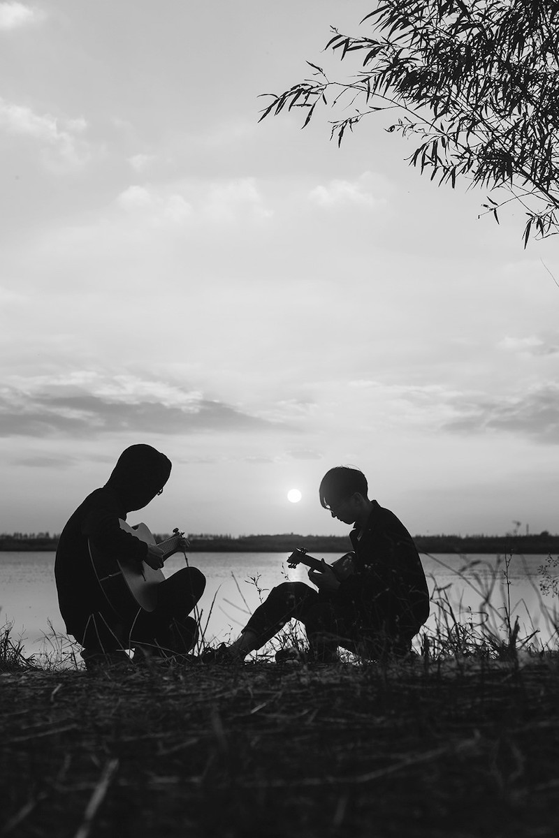 Silhouette of men playing guitar against sunset sky.