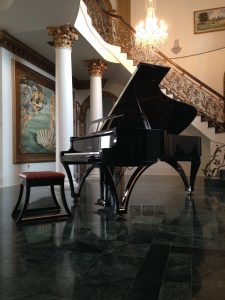 Grand piano with curved legs in a setting with an ornate staircase behind it and paintings on adjacent wall.